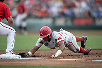 Arkansas Razorbacks outfielder Christian Franklin (25) dives back to first base during Game 5 of the NCAA College World Series against the Texas Tech Red Raiders on June 17, 2019 at TD Ameritrade Park in Omaha, Nebraska. Texas Tech defeated Arkansas 5-4. (Andrew Woolley/Four Seam Images)