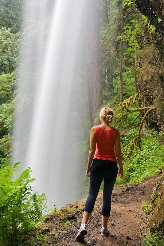 Young woman hiking at Silver Falls State Park at Middle North Falls. Oregon