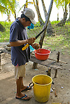 Kuna man prepares a fresh coconut on Isla Pelikano, San Blas Islands, Kuna Yala, Panama