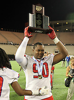 Manatee Hurricanes defensive lineman DeMarcus Christmas #90 hoists the Championship trophy after the Florida High School Athletic Association 7A Championship Game at Florida's Citrus Bowl on December 16, 2011 in Orlando, Florida.  Manatee defeated First Coast 40-0.  (Mike Janes/Four Seam Images)