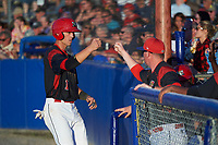Batavia Muckdogs third baseman Tyler Curtis (11) fist bumps pitching coach Jason Erickson (16) after scoring a run in the bottom of the fourth inning during a game against the Auburn Doubledays on July 4, 2017 at Dwyer Stadium in Batavia, New York.  Batavia defeated Auburn 3-2.  (Mike Janes/Four Seam Images)