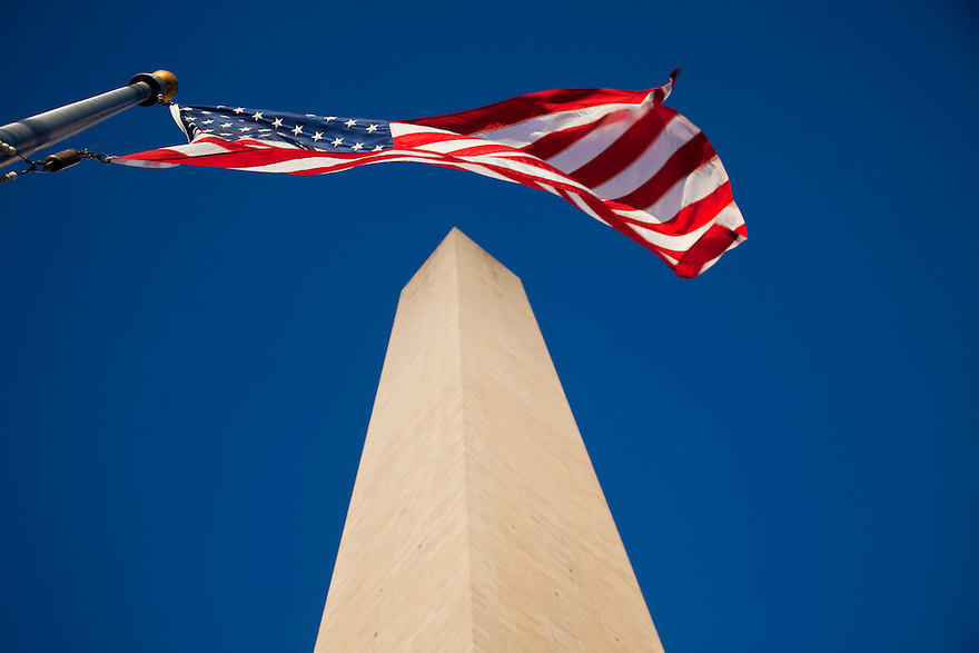 American flags surround the Washington Monument in Washington, D.C.   Completed in 1884, it was built in honor of George Washington, who led the country to independence and then became its first President.   It is shaped like an Egyptian obelisk and stands over 555 feet tall.