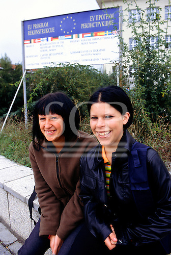 Sarajevo, Bosnia. Two smiling girl students with an EU reconstruction sign behind.