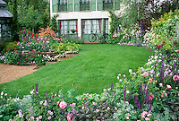 Perfect Lawn grass and beautiful flower garden perennial borders with house, roses Rosa, home landscaping, bicycle