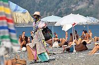 - African immigrant street vendor on the beach of Riva Trigoso (Liguria)....- venditore ambulante immigrato africano sulla spiaggia di Riva Trigoso (Liguria)