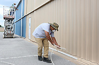 Misael Nieto paints the lower trim Wednesday, September 9, 2020, as Alonso Trujillo and his father Serafin Trujillo, all with Genaro's Painting, work on the upper section of a hanger at the Springdale Municipal Airport. The airport is painting over the blue hangers to match the color of the new hangers built at the airport. Check out nwaonline.com/200910Daily/ and nwadg.com/photos for a photo gallery.<br /> (NWA Democrat-Gazette/David Gottschalk)
