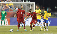 Portugal midfielder Miguel Veloso (4) works to clear ball as Brazil midfielder Ramires (16) defends. In an international friendly, Brazil (yellow/blue) defeated Portugal (red), 3-1, at Gillette Stadium on September 10, 2013.
