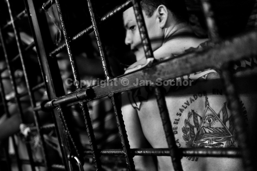 A gang member shows off his tattoo behind the bars of the cell in a detention center in San Salvador, El Salvador, 20 February 2014. During the last two decades, Central America has become the deadliest region in the world that is not at war. According to the UN statistics, more people per capita were killed in El Salvador than in Iraq, in recent years. Due to the criminal activities of Mara Salvatrucha (MS-13) and 18th Street Gang (M-18), the two major street gangs in El Salvador, the country has fallen into the spiral of fear, violence and death. Thousands of Mara gang members, both on the streets or in the overcrowded prisons, organize and run extortions, distribution of drugs and kidnappings. Tattooed armed young men, mainly from the poorest neighborhoods, fight unmerciful turf battles with their coevals from the rival gang, balancing between life and death every day. Twenty years after the devastating civil war, a social war has paralyzed the nation of El Salvador.