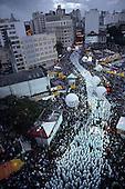 Salvador, Bahia State, Brazil. Filhos de Gandhi carnival block snaking through the spectators.