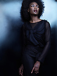 Beautiful african american woman wearing black clothes on shiny black background. High fashion photo. Image © MaximImages, License at https://www.maximimages.com
