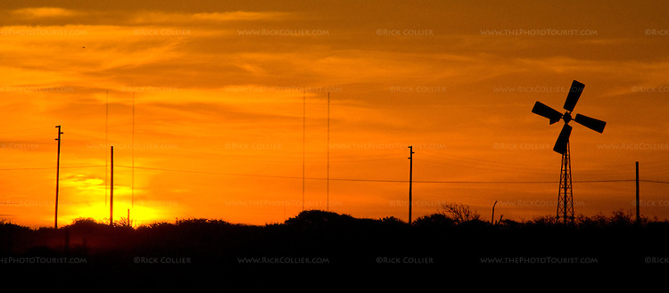 Bonaire, Netherland Antilles -- Radio towers and windmills are silhouetted against the red sky at sunset.