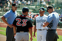 Fort Wayne TinCaps Jose Valentin #22 talks with John Tamargo #28 and umpires Dustin Klinghagen (left) and John Burzynski (right) during a game against the Lansing Lugnuts at Parkview Field on June 27, 2012 in Fort Wayne, Indiana.  Fort Wayne defeated Lansing 3-2.  (Mike Janes/Four Seam Images)
