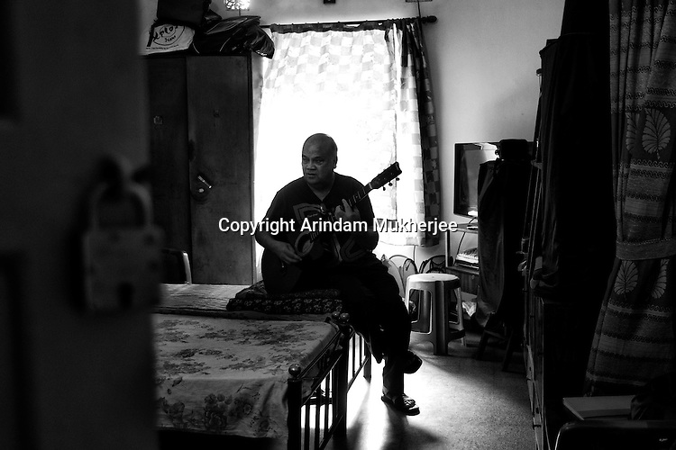 Clive Maher playing guiter at his temporary residence in Kolkata. Maher immigrated to Melbourne in the 70s and now lives there. However it's a yearly ritual for him to fly down to Kolkata to catch up with old friends and family.