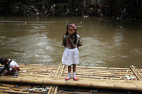 A young girl stands on a boat that takes residents across a river in a slum community in central Jakarta. Many of the city's poorest residents live just inches above the waterline throughout the city.