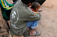 Lao PDR Oudomxay, man with Che Guevara image and german flag on jacket and son with toy pistol