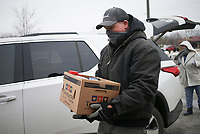 James Wilson of Lowellcarries a box of donated food, Sunday, February 22, 2021 at the Lowell City Hall in Lowell. Members of Centerpoint Church held a food collection event at two locations to collect food for the Northwest Arkansas Food Bank. The event is part of a Service Sunday program they've started to serve the community. In addition to the Lowell location, they collected food at the Rogers Public Library. Check out nwaonline.com/210222Daily/ for today's photo gallery. <br /> (NWA Democrat-Gazette/Charlie Kaijo)
