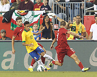 Brazil forward Neymar (10) dribbles as Portugal midfielder Miguel Veloso (4) defends. In an international friendly, Brazil (yellow/blue) defeated Portugal (red), 3-1, at Gillette Stadium on September 10, 2013.
