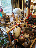 BNPS.co.uk (01202 558833)<br /> Pic: AdamPartridgeAuctioneers/BNPS<br /> <br /> Pictured: The Dining room was of course filled with pots including a Lee Kang-Hyo (circled, left) large flat stoneware bottle and a stone sculpture (circled, right) by Andy Nasisse, 'Man', covered in dark blue glaze.<br /> <br /> A huge collection of pottery and ceramics found stacked inside the suburban home of an elderly couple has sold for almost £200,000.<br /> <br /> Leonard and Alison Shurz filled every room of their three bed house with ceramic pieces they had gathered from all over the world.<br /> <br /> The Aladdin's Cave of pots, bowls, plates, vases and jugs was found by a stunned auctioneer who had the daunting task of cataloguing it all.