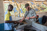 Peace Corps Volunteer Talking to Man Hulling Cashew Nuts.  Group Juboo Cashew Processing Center, Fass Njaga Choi, North Bank Region, The Gambia