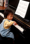 17 month old toddler girl imitation/modeling sitting at piano trying to play Asian American Vietnamese vertical