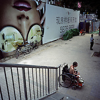 A beggar solicits money in front of a real estate advertisement in Sanlitun shopping district, Beijing, China in August, 2009. (Mamiya 6, 75mm f3.5, Kodak Ektar 160 film)