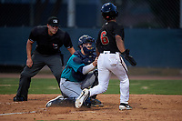 AZL Mariners catcher Brennon Kaleiwahea (13) applies the tag to Glenallen Hill Jr. (6) as home plate umpire Jesse Segura watches on during an Arizona League game against the AZL D-backs on July 3, 2019 at Salt River Fields at Talking Stick in Scottsdale, Arizona. The AZL D-backs defeated the AZL Mariners 3-1. (Zachary Lucy/Four Seam Images)