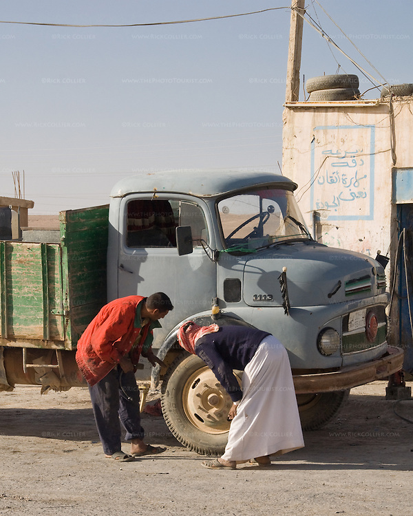"""""""Broken"""" -- A truck driver consults with the local mechanic (in traditional arab garb) at a truck stop on the """"desert highway,"""" south from Amman Jordan.  © Rick Collier"""