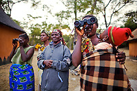 Women spot their first hippo on safari in Kasanka National Park. Local schools and women's groups are regularly brought into Kasanka, which is unique in the country and unusual in Africa as it is privately managed and owned by a trust. People are able to see animals flourishing in land which was once free reign for poachers. Combined with anti-poaching scouts, the education programme is on the frontline of conservation methods in the park, showing local people wild animals in their natural habitat.