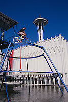 Man Rides High Rail Balance Bicycle At The Pacific Science Center; Space Needle In Background; Seattle, Washingto