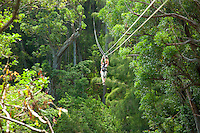 A young woman flying through the canopy of trees in the rainforest while Ziplining on the Big island with Kohala zipline