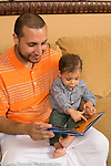 16 year old toddler boy sitting on couch with father looking at book together, baby pointing