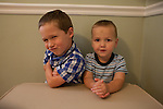 Brothers, age five, left, and age, two, right, pose for a portrait in the dining room.