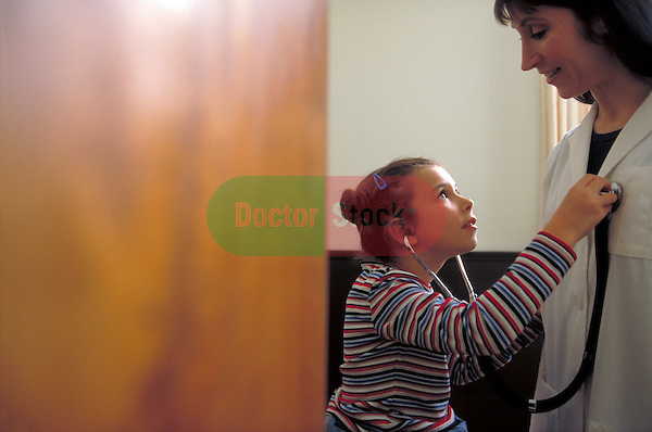 young girl examining doctor's heart with stethoscope