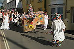 Hunting the Earl of Rone. Combe Martin Devon England.  2011. The procession led by the Hobby Horse followed by the Earlof Rone sitting backwards ona donkey and the Grenadiers process down the main street in the village.