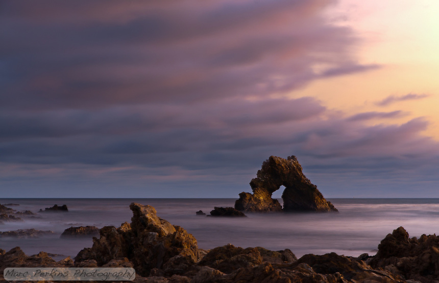 Clouds blow over the arch rock visible offshore at Little Corona.  Captured after sunset on a gorgeous day, the long exposure softens the ocean waves into a silky smooth, almost misty, layer.