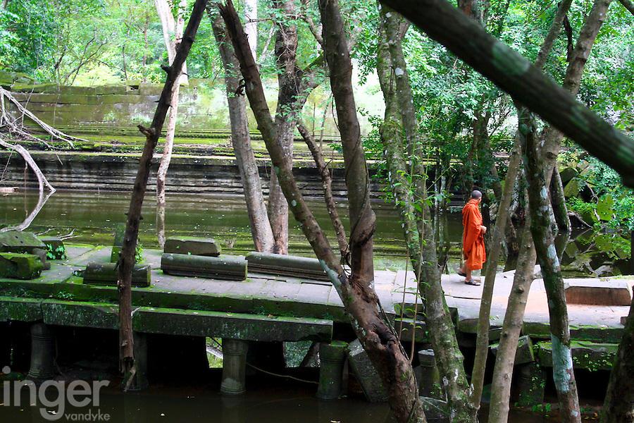 Monk walking through Beng Mealea temple in Cambodia