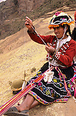 Pisac, Peru. Quechua Indian woman in traditional dress weaving a strap and spinning.