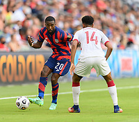 AUSTIN, TX - JULY 29: Shaq Moore #20 of the United States passes the ball around Homam Ahmed #14 of Qatar during a game between Qatar and USMNT at Q2 Stadium on July 29, 2021 in Austin, Texas.