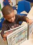 Education preschool 3 year olds boy holding picture book upside down as he looks at it
