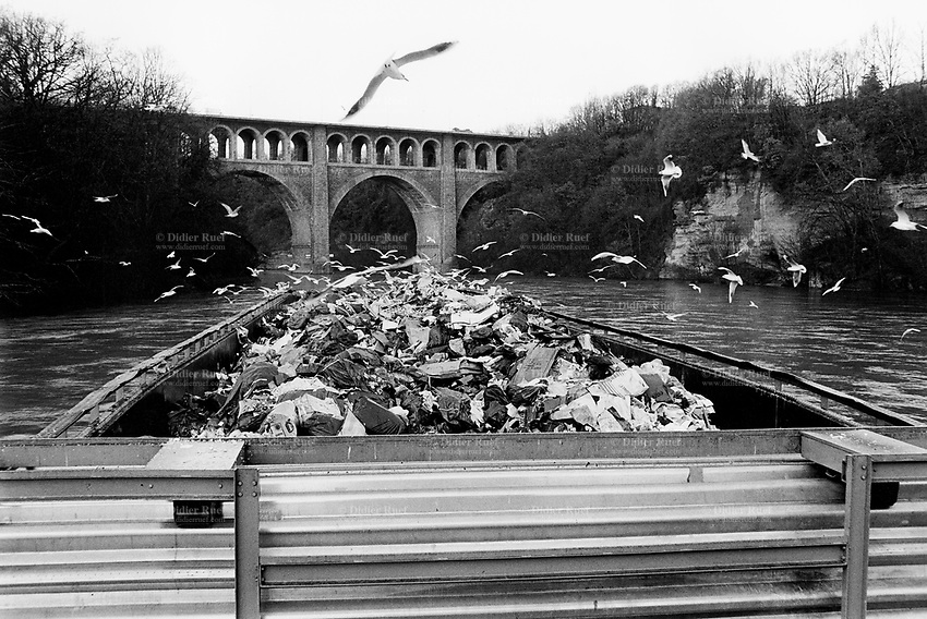 """Switzerland. Geneva. Garbage collectors. A barge, fully loaded with garbage, will sail down the current on the river Rhône to """"Les Cheneviers"""" which is the incinerating plant, distant 25 km from the town. Bilds are flying over the garbage heap. © 1991 Didier Ruef"""