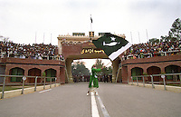The Wagah border crossing on the Grand Trunk Road. Thousands of spectators gather every day to cheer each side of the border, here the Pakistani crowd are encouraged by a man waving the national flag beneath a picture of Jinnah, founder of Pakistan.