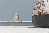 Cargo ship M/V Sam Laud in Cleveland Harbor in front of the ice covered Cleveland Harbor West Pierhead Light