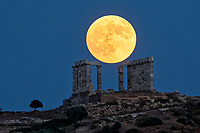A full moon rises, which turned into a blood moon lunar eclipse, over the ancient temple of Poseidon in Sounion, Greece. Friday 27 July 2018