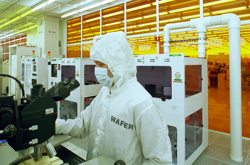 A technician wearing protective gear at work in a computer lab.