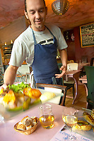 Gruissan village. La Clape. Languedoc. A waiter coming with the fish served for main course. Restaurant La Cranquette. France. Europe.