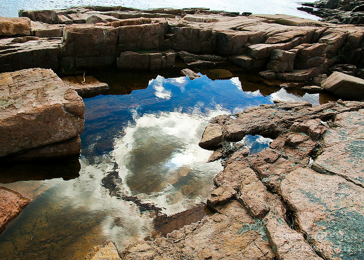 Pool of water reflecting the blue sky and clouds just after a rain storm in Acadia National Park in Maine.  Red rocks are near Sand Beach in east end of Park.
