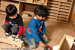 Education preschool 3-4 year olds block area parallel play two boys working separately playing with blocks and human figures horizontal