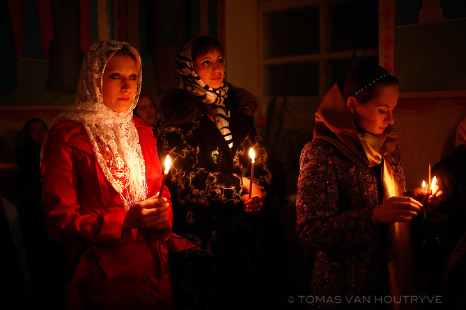Women hold candles during the Orthdox Easter church service in the village of Chobruchi, Transnistria on 19 April 2009.