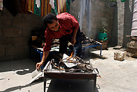 """Gaza.June.22.2008 Um suhil  cooked using wood fire with her sun, Um Suhail says: """"we got used to live among the graves of the deadÖ we are like them; depending on charities and handouts.""""""""The family was drove out from their original village in the 1948 when Jews forced thousands of Palestinians to migrate, establishing the State of Israe.June.22.2008l.""""photo by Fady Adwan/propaimages"""""""