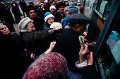 """Moscow, Russia<br /> October 22, 1992<br /> <br /> People fight to purchase cigarettes, for resale, at a kiosk near Kievski train station. The early days of the """"rezbourka"""", a business sorting out that left many dead throughout Russia in the 1990's.<br /> <br /> In December 1991, food shortages in central Russia had prompted food rationing in the Moscow area for the first time since World War II. Amid steady collapse, Soviet President Gorbachev and his government continued to oppose rapid market reforms like Yavlinsky's """"500 Days"""" program. To break Gorbachev's opposition, Yeltsin decided to disband the USSR in accordance with the Treaty of the Union of 1922 and thereby remove Gorbachev and the Soviet government from power. The step was also enthusiastically supported by the governments of Ukraine and Belarus, which were parties of the Treaty of 1922 along with Russia.<br /> <br /> On December 21, 1991, representatives of all member republics except Georgia signed the Alma-Ata Protocol, in which they confirmed the dissolution of the Union. That same day, all former-Soviet republics agreed to join the CIS, with the exception of the three Baltic States."""